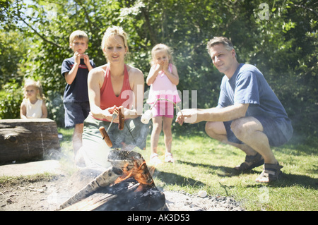 Family gathered around the campfire - Stock Photo