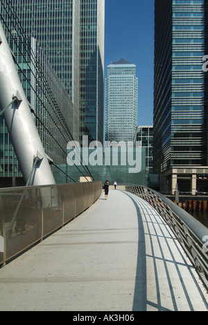 Pedestrian walks on modern footbridge towards One Canada Square landmark skyscraper at Canary Wharf Isle of Dogs - Stock Photo