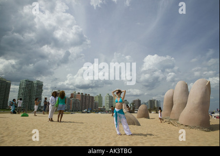 A woman wearing pants and a bikini top poses in front of the Dedos Fingers on the Playa Brava, Punta Del Este, Uruguay - Stock Photo