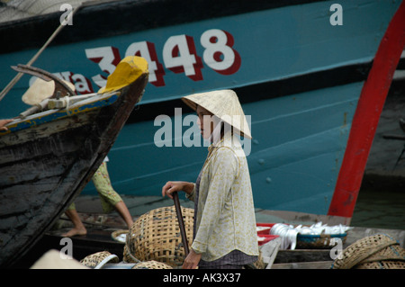 Woman wearing a cone shaped hat stands between boats Hoi An Vietnam - Stock Photo