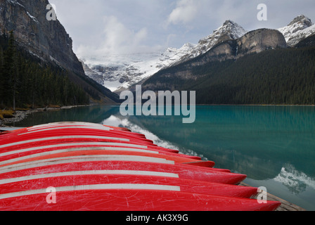 Beached red canoes at blue Lake Louise and snow on Canadian Rocky Mountains Banff National Park Alberta Canada - Stock Photo