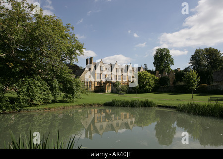 Stanway House in the Cotswold village of Stanway reflected in its lake on a summers day - Stock Photo
