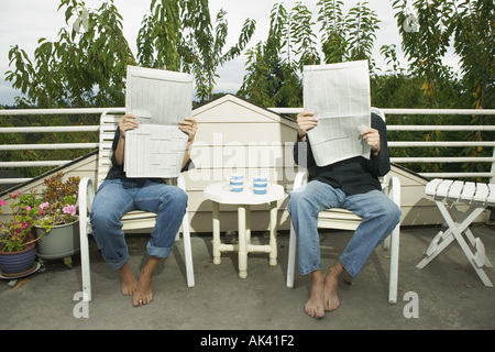 A couple reading newspapers on their porch - Stock Photo