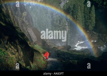 Hiker under rainbow on Mist Trail, Yosemite NP, California - Stock Photo