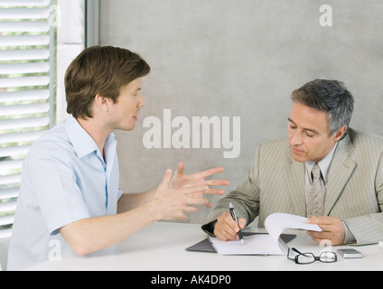Young man speaking to mature businessman and gesturing - Stock Photo