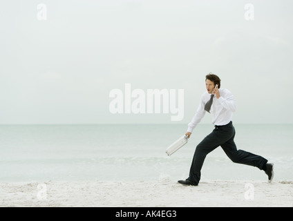 Businessman running on beach, with cell phone and briefcase - Stock Photo