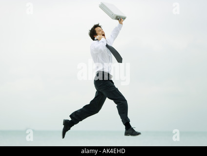Businessman running and jumping, with cell phone and briefcase - Stock Photo