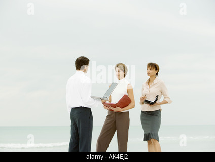 Businessman with laptop facing women with agendas, on beach - Stock Photo