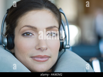 Woman wearing headphones and using neck pillow, close-up - Stock Photo