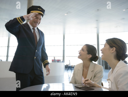 Airline pilot saluting two female travelers - Stock Photo
