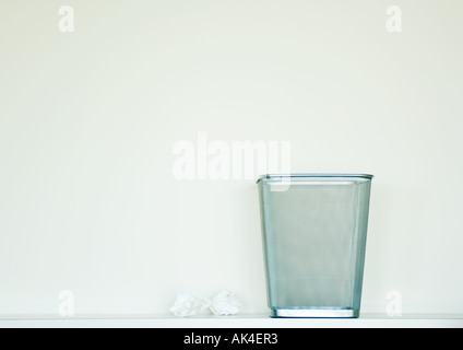 Empty wastepaper basket next to crumpled balls of paper - Stock Photo