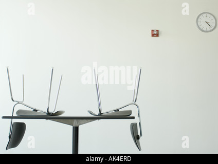 Chairs upside down on table in breakroom - Stock Photo