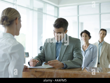 Man signing at reception desk while people wait in line behind him - Stock Photo