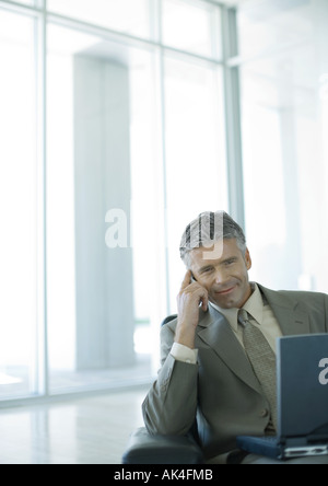 Businessman using cell phone and laptop in lobby - Stock Photo