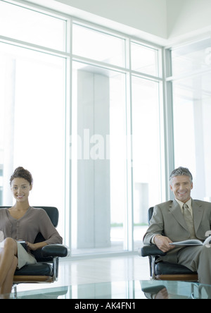 Two business professionals sitting in office lobby, smiling at camera - Stock Photo