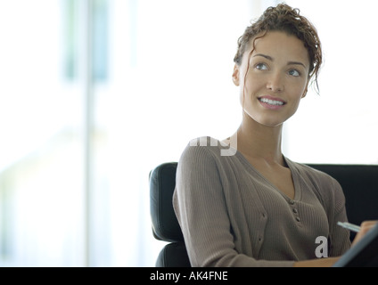 Woman writing and looking up - Stock Photo