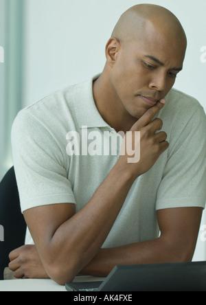 Man sitting at desk, looking at laptop and furrowing brow - Stock Photo