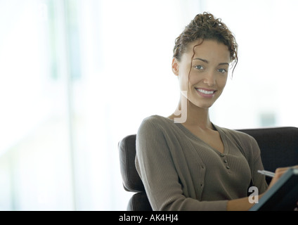 Young businesswoman smiling at camera - Stock Photo