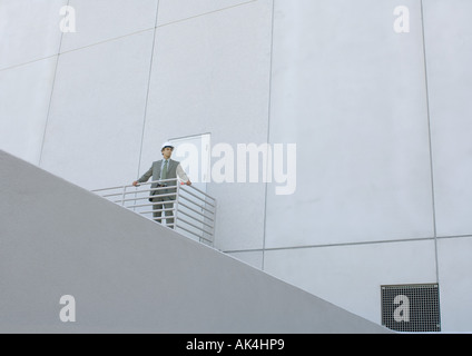 Achitect standing next to building, low angle view - Stock Photo