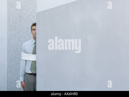 Businessman tied up, standing partially hidden behind wall - Stock Photo
