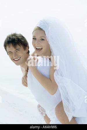 Bride riding piggyback on groom's back - Stock Photo