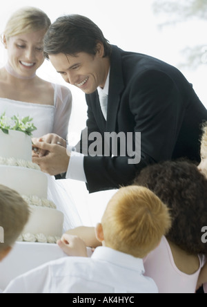 Groom cutting wedding cake - Stock Photo