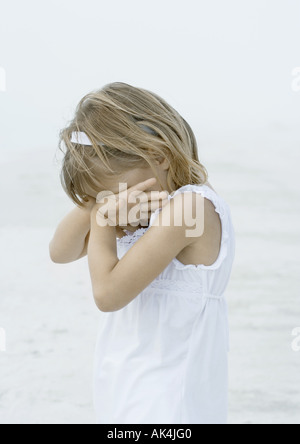 Girl covering face on beach - Stock Photo