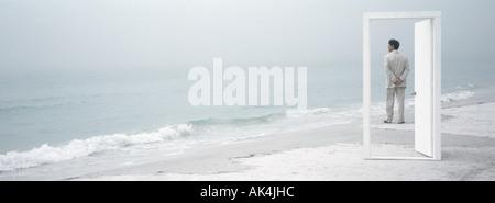 On beach, man seen through open doorway, looking at view - Stock Photo