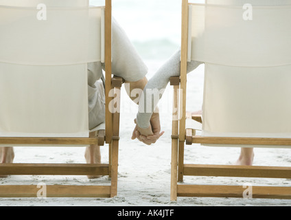 Couple sitting in beach chairs, holding hands, rear view - Stock Photo