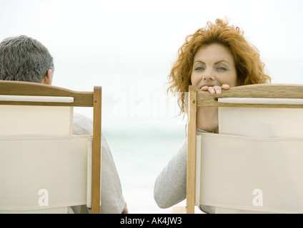 Couple sitting in beach chairs, woman turning around, looking at camera - Stock Photo