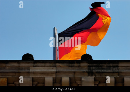 german flag on top of the Reichstag blowing in the wind Berlin - Stock Photo