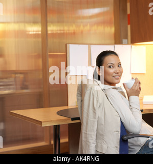 Young woman executive day dreaming in office - Stock Photo