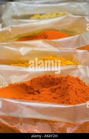 Ground orange chillies and turmeric for sale from plastic sacks in the market at Paharaganj main bazaar, New Delhi. - Stock Photo