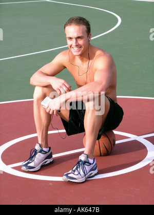 A man rests on a basketball court in a park  - Stock Photo
