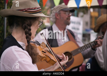 Violinist and guitar players in bluegrass group Seattle Washington University District outdoor farmers market - Stock Photo