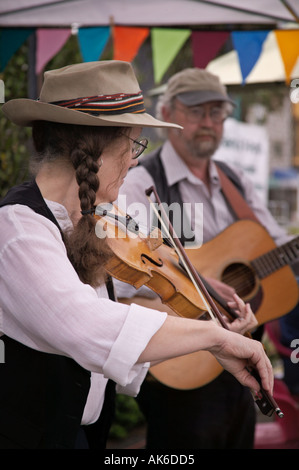 Violin and guitar players in bluegrass group Seattle Washington University District outdoor farmers market - Stock Photo