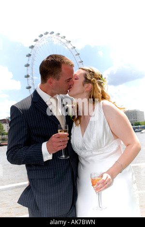 Freshly married young white couple kissing on boat holding glasses of champagne. London Eye in background during - Stock Photo