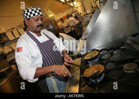 A chef cooks an indian dish in a London restaurant - Stock Photo