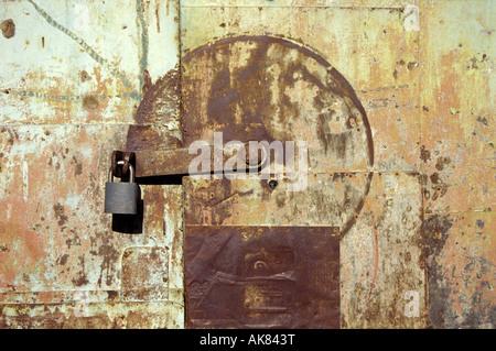 Padlock and swivel latch on a rusty metal door, Real de Catorce, Mexico - Stock Photo