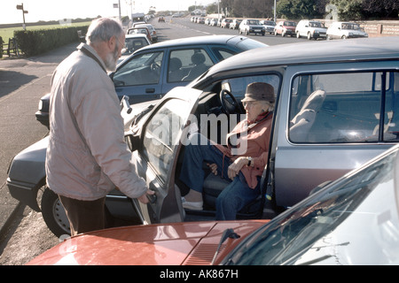 elderly son assisting mother out of the car - Stock Photo