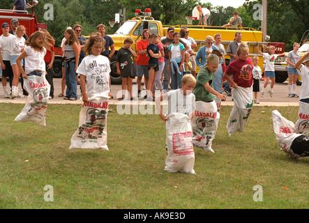Kids age 11 in potato sack race in Watermelon Days Festival. Vining Minnesota USA - Stock Photo