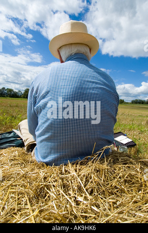 Lone figure sitting on a pile of straw in a field