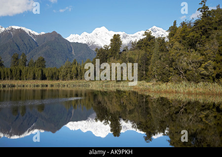 Summits of Mt Tasman centre and Aoraki Mt Cook right reflected in Lake Matheson Westland National Park West Coast - Stock Photo