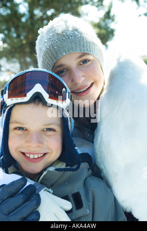 Brother and sister smiling at camera, cheek to cheek, dressed in winter clothing, portrait - Stock Photo
