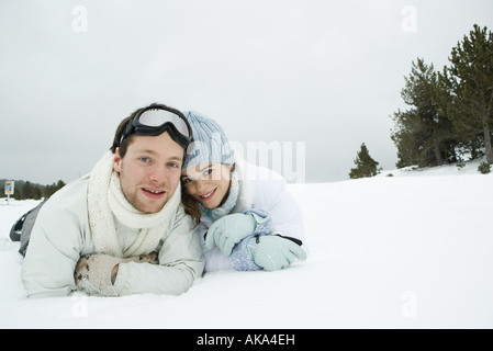 Young couple lying side by side in snow, smiling at camera, portrait - Stock Photo