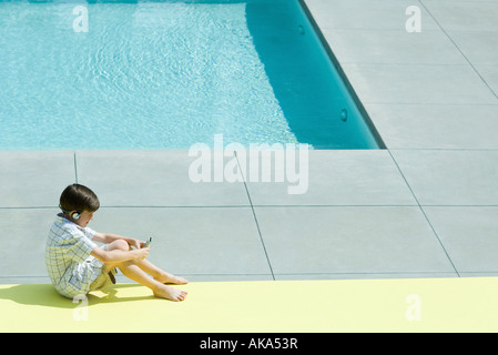 Boy sitting on the ground next to swimming pool, using handheld electronic device, wearing headphones - Stock Photo
