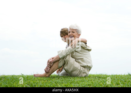 Senior woman and grandson sitting on grass, smiling at camera, full length