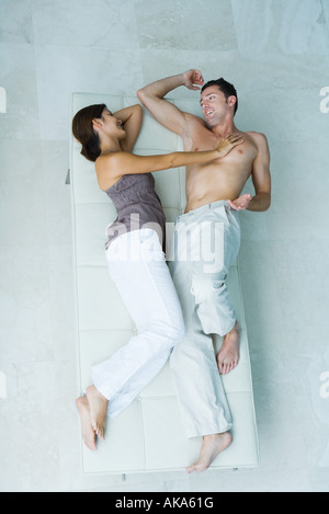 Couple lying on chaise longue together, woman pushing man away, full length, view from above - Stock Photo