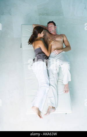 Couple lying on chaise longue together, smiling at each other, woman's hand on man's bare chest, full length, view - Stock Photo