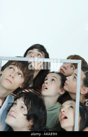 Group of young friends holding up picture frame, looking up, portrait - Stock Photo